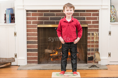 Portrait of a young smiling boy in front of a fireplace dressed for valentine's day Stock Photo