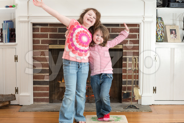 Portrait of a two young smiling sibling girls in front of a fireplace dressed for valentine's day Stock Photo