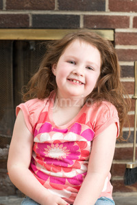 Portrait of a young smiling girl in front of a fireplace dressed for valentine's day Stock Photo