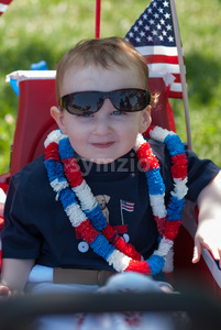 Young boy riding in red wagon having fun in the park for July Fourth Stock Photo
