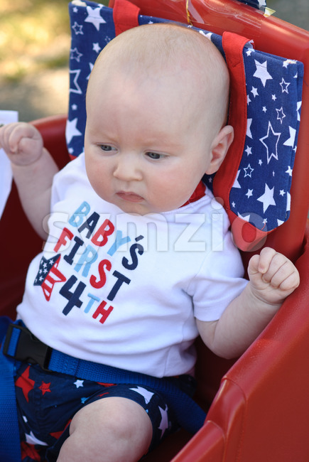 A Young infant boy riding in red wagon having fun in the park for July Fourth