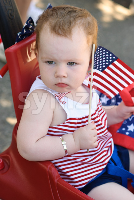 Young girl holding an American flag and riding in red wagon having fun in the park for July Fourth Stock Photo