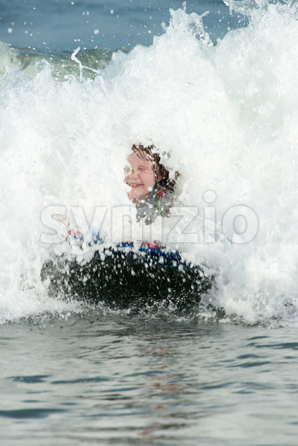 Young Girl surfing the waves on a boogy board Stock Photo