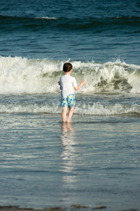 Young cute little boy playing at the seaside running into the surf on a sandy beach in summer sunshine Stock Photo
