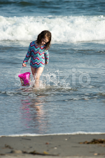 Young cute little girl playing at the seaside carrying a red bucket at the edge of the surf on a sandy beach in summer sunshine Stock Photo
