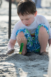 Young little boy playing with the sand and building sandcastle at the beach near the sea. Stock Photo