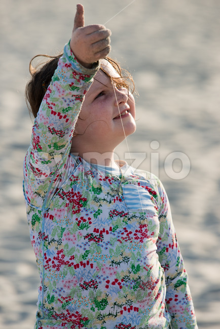 Young girl on beach with kite smiling Stock Photo