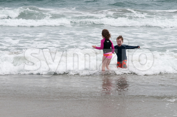 Young cute little boy and girl playing at the seaside running into the surf on a sandy beach in summer sunshine Stock Photo
