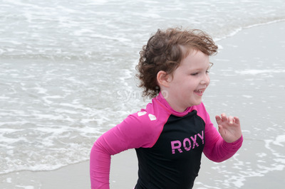 Young cute little girl playing at the seaside running into the surf on a sandy beach in summer sunshine Stock Photo