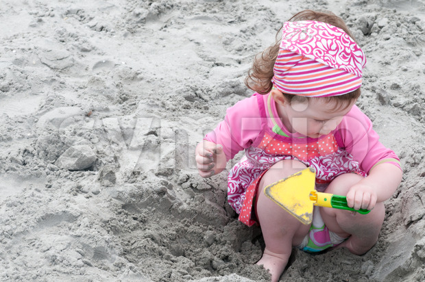 Young little girl playing with the sand and building sandcastle at the beach near the sea. Stock Photo