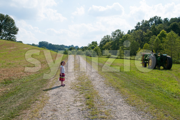 Girl on dirt pathway surrounded by green open space with mature trees on a sunny day with light clouds at Stroud Preserve Stock Photo