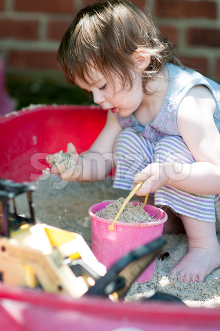 Adorable little girl playing in a sandbox Stock Photo