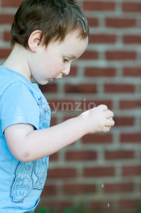 Young toddler boy in front of red birck wall Stock Photo
