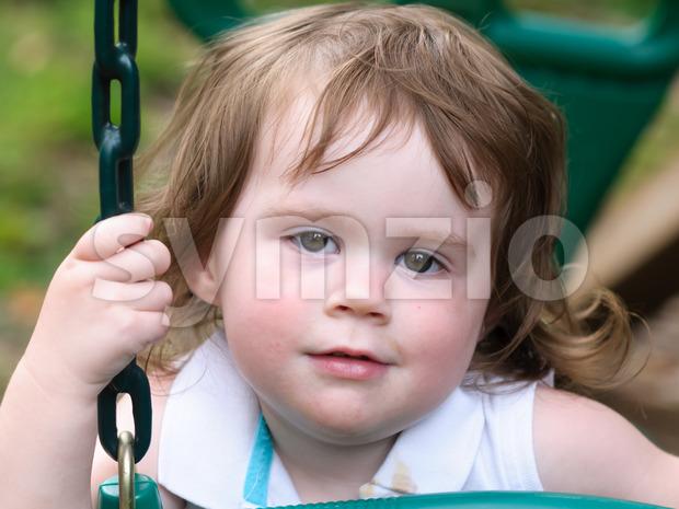 A young girl having fun on a swing