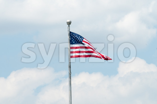 Flag of the United States of America with blue sky and clouds behind it Stock Photo