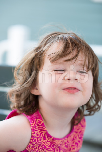 squinting expression little girl sitting down making funny face Stock Photo