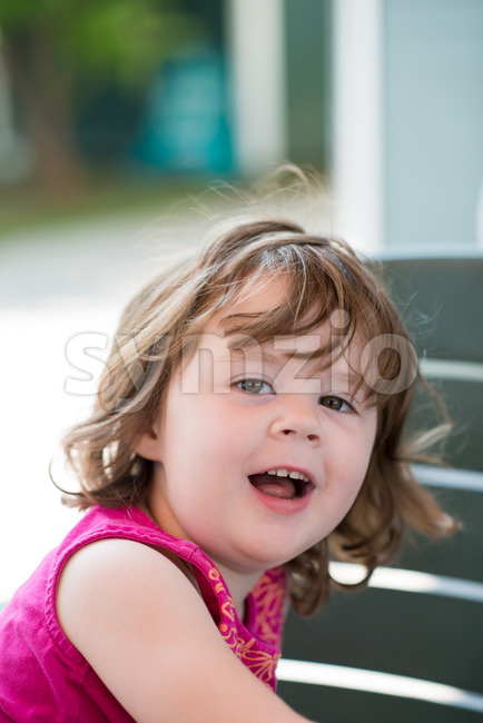 young little girl sitting down and looking happy Stock Photo