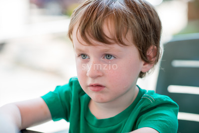 young little boy sitting down outside Stock Photo