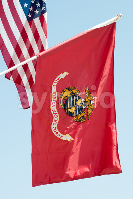 United States Marine Corps flag waving on blue sky background, close up, with American flag in background Stock Photo