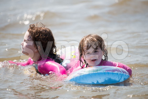 View of two young girls floating in inner tubes in a blissful state