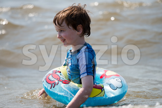 young boy floating in inner tubes in a blissful state Stock Photo
