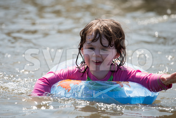 young girl floating in inner tubes in a blissful state Stock Photo