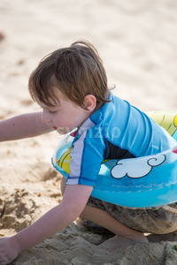 Young little boy playing with the sand and building sandcastle at the beach near the bay. Stock Photo