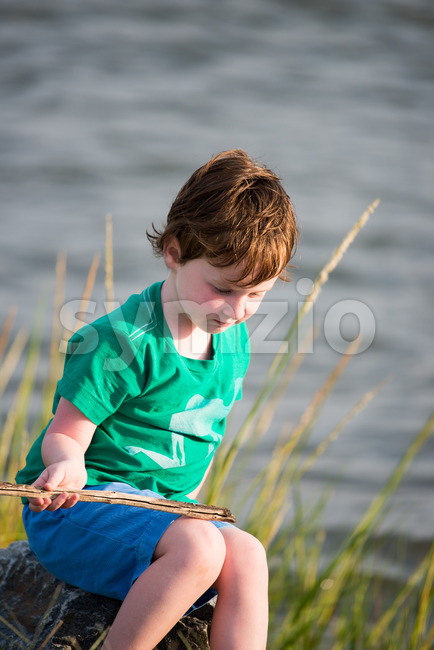 Young boy holding stick from among the reeds along the bay Stock Photo