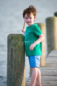 young boy standing on a wooden rustic dock holding a stick on a warm summer day. Stock Photo