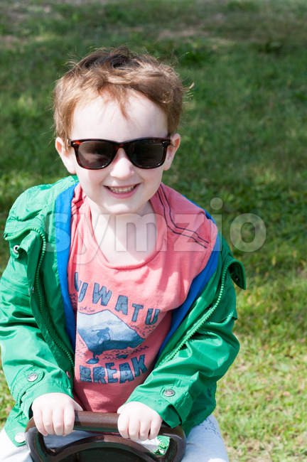 Voew of Happy little boy is swinging on see-saw wearing oversized sunglasses