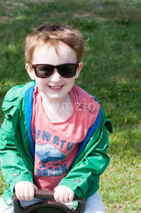 Happy little boy is swinging on see-saw wearing oversized sunglasses Stock Photo