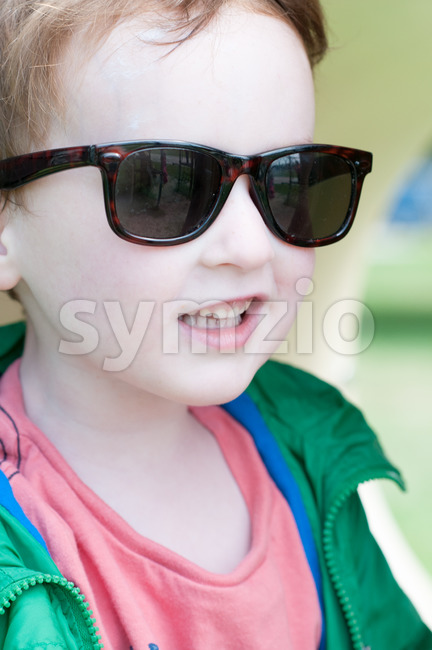 View of Happy little boy is swinging on see-saw wearing oversized sunglasses