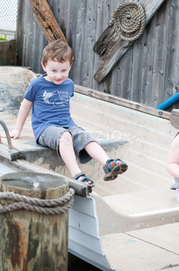 An adorable boy happily sitting in a small row boat next to mooring posts Stock Photo