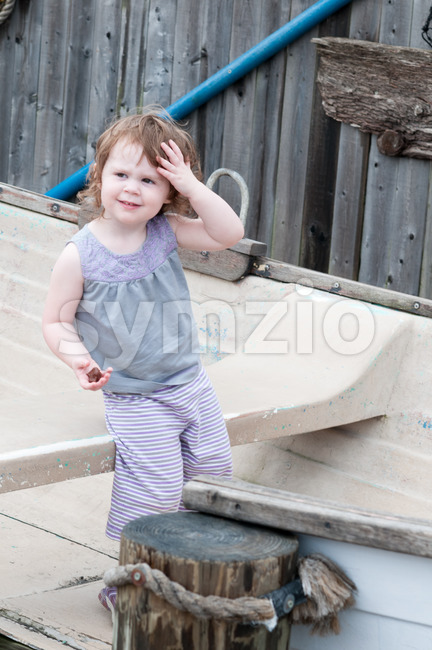 An adorable girl happily sitting in a small row boat next to mooring posts Stock Photo
