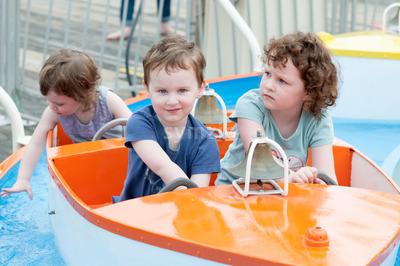 Young toddler sibblings having fun on boardwalk amusement ride Stock Photo