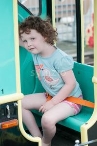 Young toddler girl having fun on boardwalk amusement ride Stock Photo