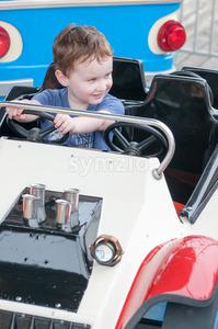 Young toddler boy having fun on boardwalk amusement ride Stock Photo