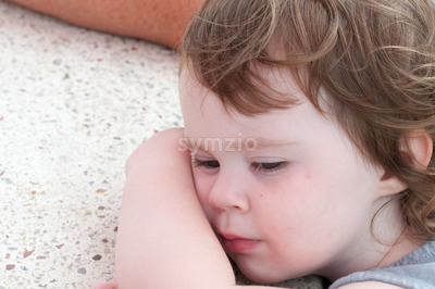 Cute young toddler girl falling asleep resting her head on table Stock Photo