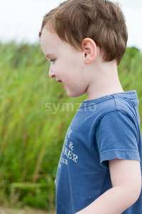 Profile of young boy walking outside along beach sand dunes with reeds Stock Photo