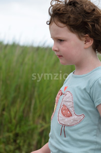 Profile of young girl walking outside along beach sand dunes with reeds Stock Photo