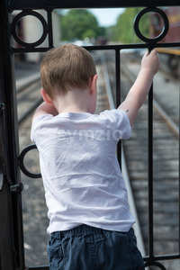 Young boy standing at back of train looking down at track Stock Photo