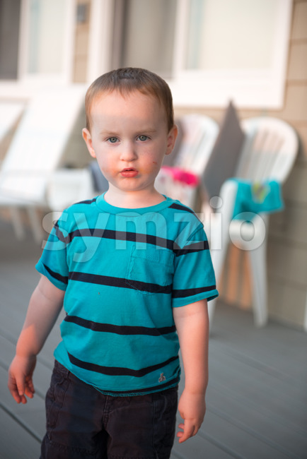 View of Young toddler boy on patio deck outside at sunset down at shore