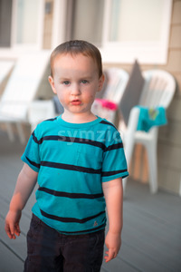 Young toddler boy on patio deck outside at sunset down at shore Stock Photo