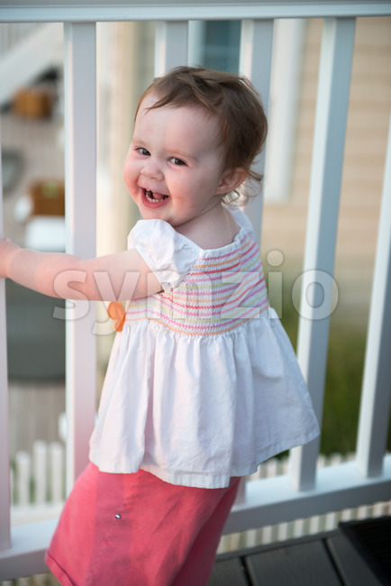 Young toddler girl on patio deck outside at sunset down at shore Stock Photo