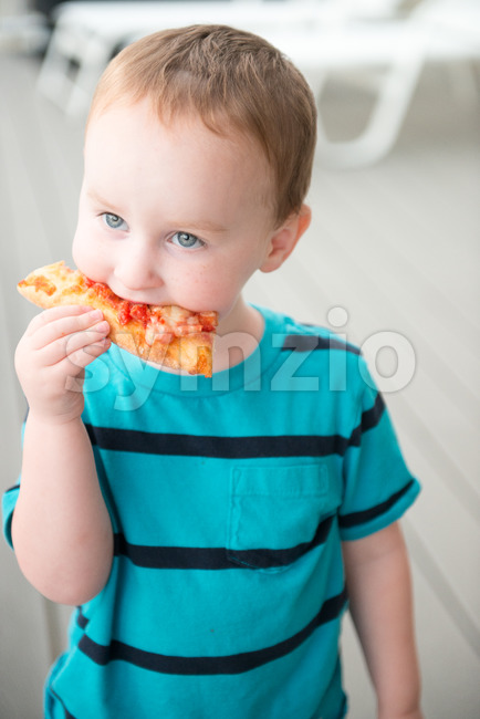 Young toddler boy on patio deck outside at sunset down at shore eating pizza Stock Photo