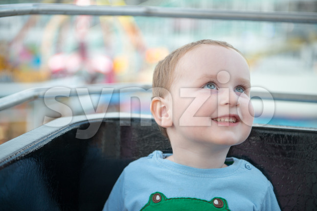 Young boy on boardwalk amusement ride ferris wheel looking up Stock Photo