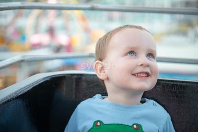 Young boy on boardwalk amusement ride ferris wheel looking up Stock Photo