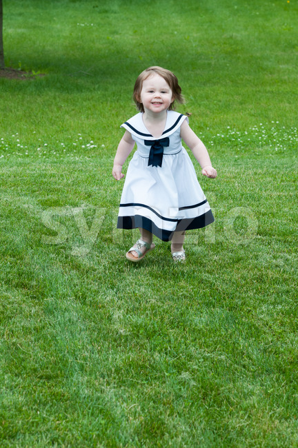 Portrait of a cute adorable little girl child in dress running on grass Stock Photo