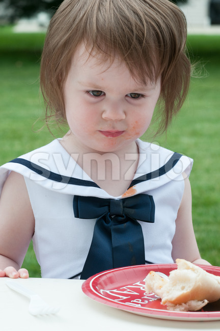 Young girl in fancy dress outside eating Stock Photo