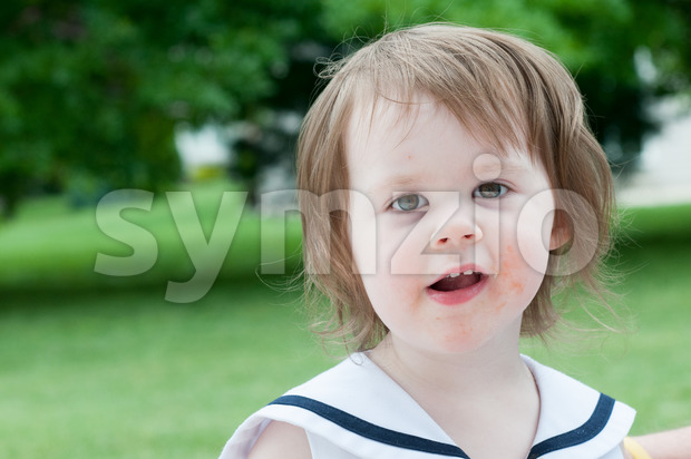 Portrait of a cute adorable little girl child in dress outside Stock Photo
